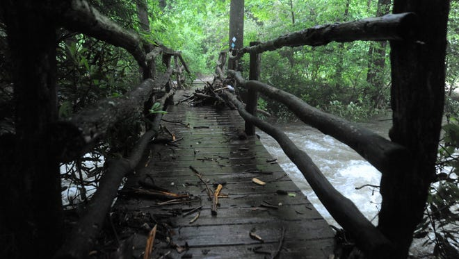 A foot bridge in Montreat is covered with debris after flood waters recede on May 30.