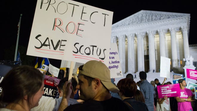 A demonstrator holds a sign as protesters gather in front of the Supreme Court in Washington, Monday, July 9, 2018, after President Donald Trump announced Judge Brett Kavanaugh as his Supreme Court nominee.. (AP Photo/Cliff Owen)