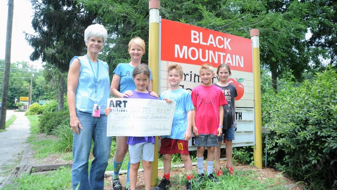 Children in the Art In the Afternoon program in present an $800 check to Black Mountain Primary School principal Malorie McGinnis. The money, which was raised by the program's annual art show at the Black Mountain Library, will go toward the construction of a new playground at the school. Emerson Kearnes (holding the check), Lyle Sulzman, Derek Osborne, Wren Boyd and Art In the Afternoon director Stephanie Sulzman (next to McGinnis), presented the check on July 19.