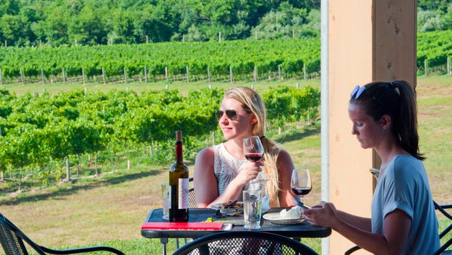Guests enjoy the new outdoor patio at Sharrott Winery in Winslow.