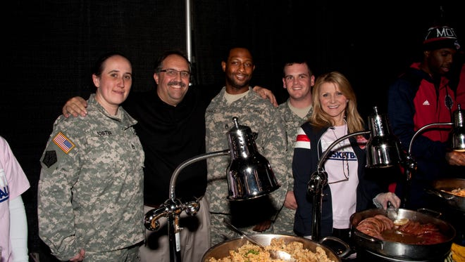 Pistons coach Stan Van Gundy and his wife, Kim, are pictured with members of the U.S. Army during a Thanksgiving dinner Tuesday at the Palace.