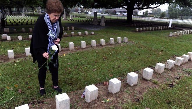 In this Oct. 12, 2014 photo, Gloria Ramsaur places a rose at the grave site of her great, great, uncle William G. Hightower at McGavock Confederate Cemetery during a Civil War descendants reunion in Franklin, Tenn. Hightower was killed at the Battle of Franklin in 1864. (AP Photo/The Tennessean, Shelley Mays)