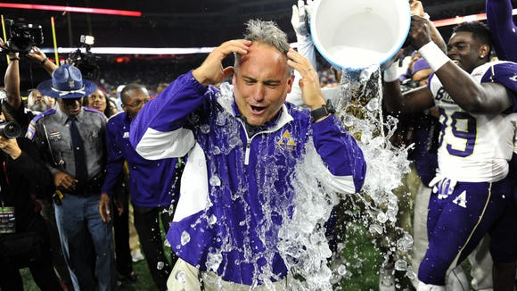 Alcorn State head coach Jay Hopson is drenched with water by tight end Metise Moore after Alcorn State defeated Southern, 34-28, in a Southwestern Athletic Conference championship NCAA college football game, Saturday, Dec. 6, 2014, in Houston. (AP Photo/Eric Christian Smith)