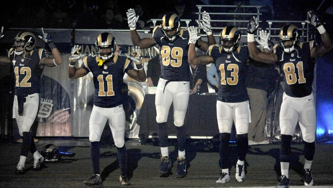 """Members of the St. Louis Rams raise their arms in awareness of the events in Ferguson, Mo.,  as they walk onto the field during introductions before an NFL football game against the Oakland Raiders, Sunday, Nov. 30, 2014, in St. Louis. From left are Stedman Bailey (12), Tavon Austin (11), Jared Cook, (89) Chris Givens (13) and Kenny Britt (81). The players said after the game, they raised their arms in a """"hands up"""" gesture to acknowledge the events in Ferguson. (AP Photo/L.G. Patterson)"""
