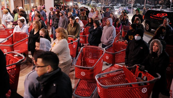 Shoppers wait outside Target in Lisbon, Conn., before the store opens for Black Friday at midnight in 2011.
