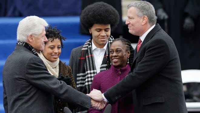 Former President Bill Clinton administers the oath of office to Mayor-elect Bill de Blasio as his wife Chirlane McCray, second from right, and their children Dante and Chiara watch on the steps of City Hall Jan. 1, 2014, in New York.
