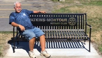 Chris Burns, past president of the Watkins-Montour Rotary Club, shows one of the new benches installed by Rotarians and the Watkins Glen High School Interact Club.