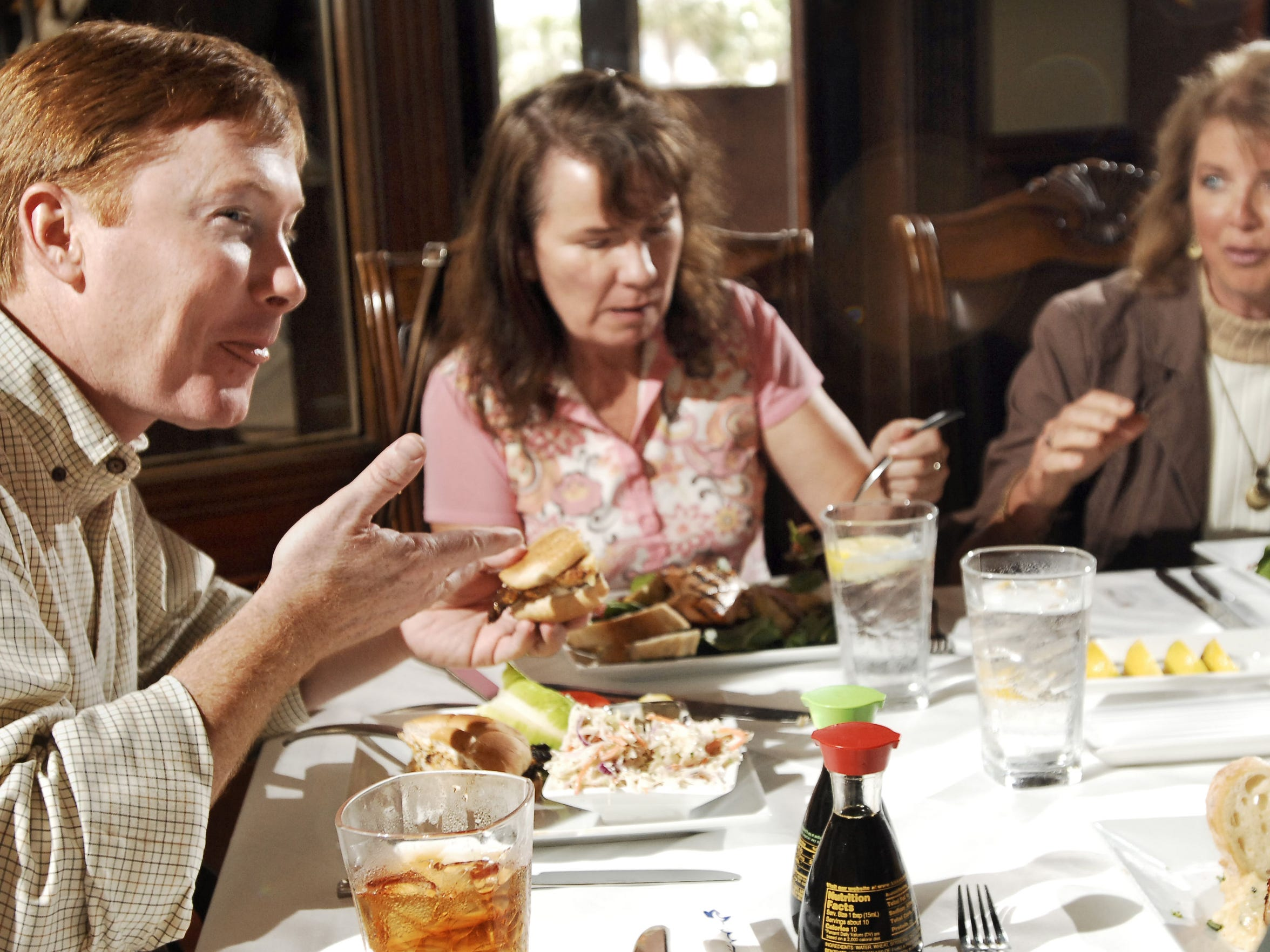 Florida Agriculture Commissioner Adam Putnam, left, talks with Centerline Solutions consultant Janet Walsh, center, and Cindy Anderson with the Panhandle Fresh Marketing Association, while eating a blackened grouper sandwich during a lunch meeting at The Fish House. Putnam met with business leaders, consultants, farmers and agricultural leaders over a seafood lunch on the one-year anniversary of the BP oil spill, emphasizing the fact that state testing has determined local seafood to be safe to eat.