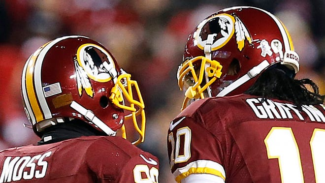 Wide receiver Santana Moss, left, and quarterback Robert Griffin III talk during Monday's game.