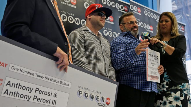 Anthony Perosi, second from right, holding a copy of the winning Powerball ticket.
