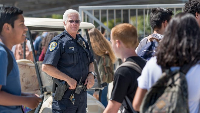 Police officer Rob Zieg watches students on campus during the lunch hour at El Diamante High School in Visalia, California, on Sept. 18, 2017. The passing of Senate Bill 707 in 2015 made it a crime to possess a firearm in a school zone except with the written permission of the school district.