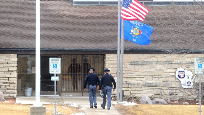 Two Wisconsin State Patrol officers walk into the State Patrol Northeast District 3 headquarters in Fond du Lac, Wednesday, March 25, where flags are at half mast after the death of trooper Trevor Casper during a shootout with a suspected bank robber Tuesday, on the cities west side.