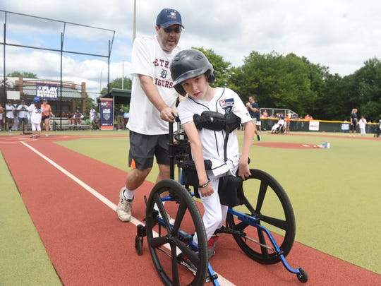 Tom Lozon, of St. Clair Shores, helps his son Jonathan toward first base during the Miracle League of Michigan baseball clinic with Detroit Tigers players on Saturday July 15, 2017 in Southfield.