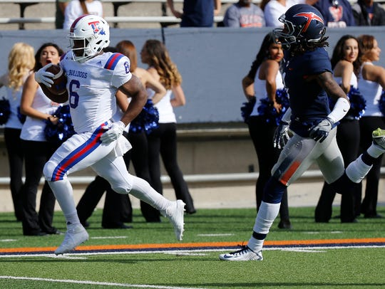 La Tech running back Boston Scott beats a UTEP defender