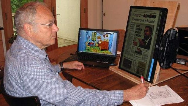 Dr. Miller reading e-paper and doing Suduko puzzle /