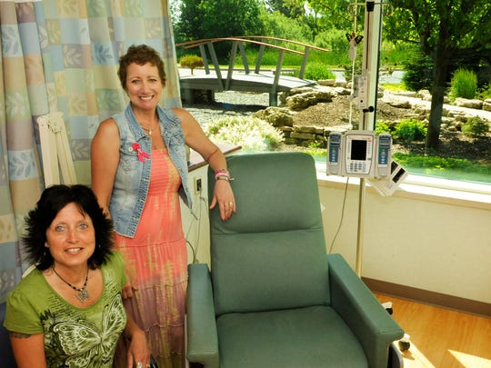 """Cancer survivor Patsy Walesh, standing, often was accompanied to the Lombardi Cancer Clinic with one of her """"chemo buddies,"""" including Tracy Rusch, seated. Walesh hopes her remission will last and she won't have to ever sit in the chair again while getting chemotherapy."""