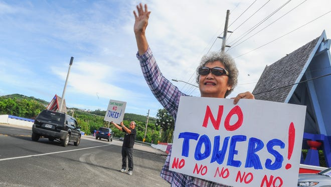 In this July 6, 2016, file photo, Barbara Santos waves to motorists near the bridge at Pago Bay.