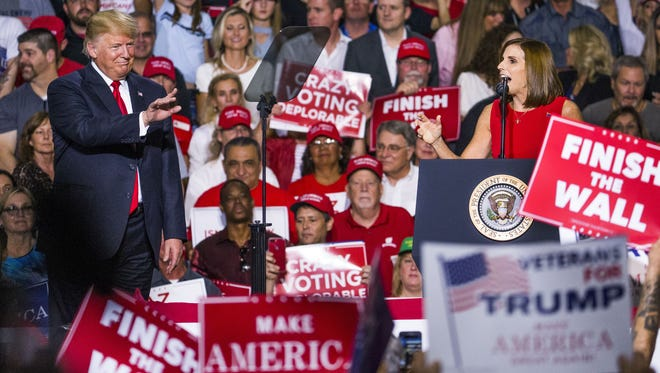 President Donald Trump joins Rep. Martha McSally on stage at the International Air Response Hangar at Phoenix-Mesa Gateway Airport on Oct. 19, 2018. President Donald Trump spoke at the rally supporting Senate candidate Rep. Martha McSally.