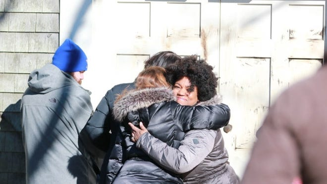 Charity-Grace Mofsen, right, who was associate director of operations at the African Meeting House at the time, gets a hug after Nantucket community members showed up to scrub racist graffiti from the front of the building in 2018.