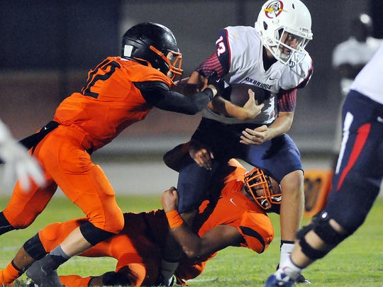 Oxbridge Academy's #2Angelo Navaroli is sacked by Cocoa High defenders during Thursday nights spring football game held at Tiger Stadium .