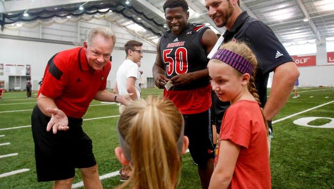 Louisville's coach Bobby Petrino jokes around with Jenna Nunn, center, and her sister Ellie. July 18, 2015