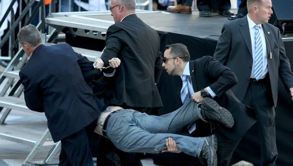 Secret Service agents remove a man from the crowd during