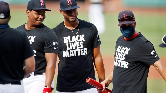Boston's Rafael Devers, left, and Xander Bogaerts, center, wear Black Lives Matter jerseys during warmups Friday night.