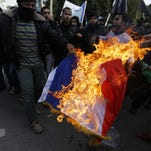 "A Palestinian Salafist burns a French national flag during a protest against the printing of satirical sketches of the Prophet Mohammed by French satirical weekly Charlie Hebdo on January 19, 2015 on their way to the French Cultural Centre in Gaza city. The walls of Gaza's French Cultural Center were painted on January 16 with graffitti in reaction to a cartoon published in the latest issue of Charlie Hebdo showing on its cover the prophet Mohammed holding a ""Je Suis Charlie"" (I am Charlie) sign under the headline ""All is forgiven""."