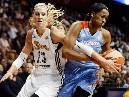 Connecticut's Katie Douglas, left, tangles with Atlanta's Swin Cash, right, during the first half of a WNBA basketball game, Sunday, June 1, 2014, in Uncasville, Conn. (AP Photo/Jessica Hill)