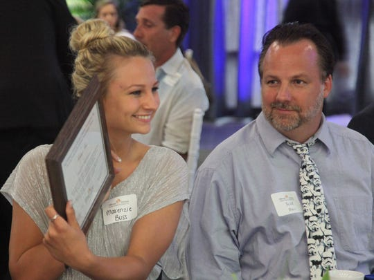 Scott Buss, right, and Makenzie Buss, of Cape Coral High School, are all smiles as she holds up her scholarship award during the Hillmyer-Tremont scholarship banquet at FGCU's Cohen Center on Monday.