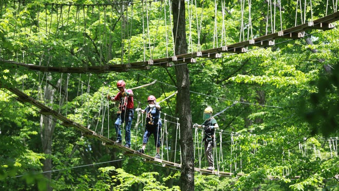 """At Hocking Hills Canopy Tours, a masked and shielded Kyle Rowland, right, leads zip liners Jerry and Georgie Hughes across a sky bridge. Now that it's reopened, the popular tourist spot is seeing plenty of interest. Customer are """"stir crazy, and they're ready to get out,"""" zip line course manager Eric Lapchenko said."""