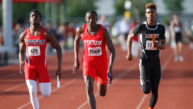 Lawrence Wallace (center) anchors the 4x100 relay for Tucson High during the high school track and field state championships at Mesa Communtiy College May 6, 2015.