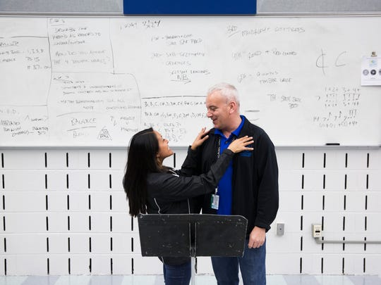 Annabelle Sarmiento, the band director at Palmetto Ridge High School, and Brett Robinson, who fills the same role at Barron Collier High School, joke around as the two pose for a photograph. The rival band directors recently got engaged and are planning their wedding.