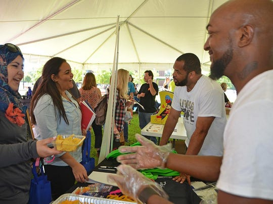 "MTSU seniors Ala El-Assuli, left with nachos and cheese, and Dana Albawab of Murfreesboro share a laugh with Christiana-based Believers' Faith Fellowship Pastor Jason Scales, second from right, and church music director Joshua Jamerson Aug. 25 during ""Meet Murfreesboro"" in the Student Union Commons. El Assuli is a special education major originally from Dubai while Albawab is a finance/insurance major originally from Jordan."