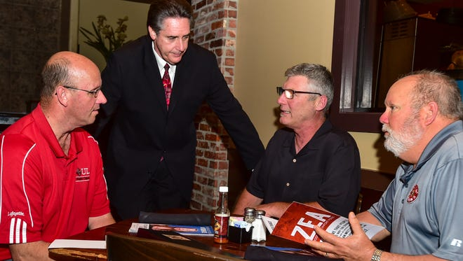 Leonard Louvierre, standing, greets Zea Rotisserie & Grill customers Mel Guidry, left, Ricardo Johnson and Stan Aucoin. Junior Achievement of Acadiana named Louvierre  the 2016 Business Person of the Year.