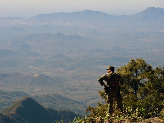 A Mexican soldier looks at the sierra of Sinaloa at the Surutato community in Sinaloa state, Mexico on Dec. 8, 2016.