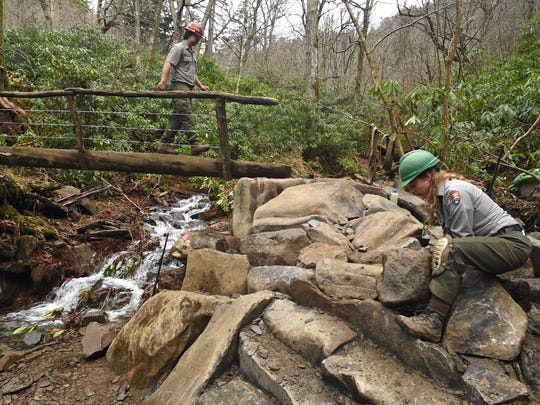 Trails Forever crew members Dakota Rogers and Kelly Grzasko, from left, work to stabilize the base of a log bridge on the Alum Cave Trail in Great Smoky Mountains National Park on Thursday, Nov. 5, 2015. (ADAM LAU/NEWS SENTINEL)