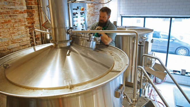 Andrew Rutherford, head brewer at Stitch House Brewery, cleans a brewing tank at the new brewery opening soon on North Market Street.