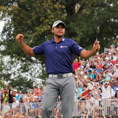 Jason Day of Australia poses with the winner's trophy on the 18th green after his six-stroke victory at The Barclays at Plainfield Country Club.