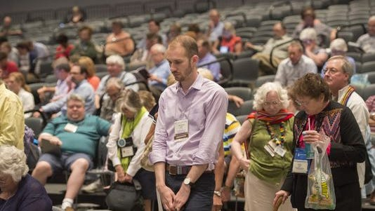 The audience takes part in an opening prayer at the 221st General Assembly of the Presbyterian Church at Cobo Hall, in Detroit, June 19, 2014.