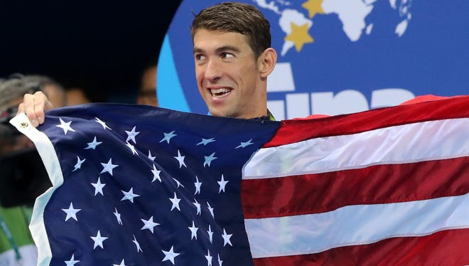 United States' Michael Phelps walks with the U.S. flag during the medal ceremony for the men's 4x100-meter medley relay final Saturday.
