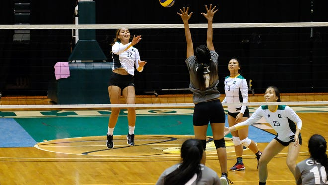 Muneka Taisipic, 12, goes for a spike above the hands of GCC's middle blocker as Lori Okado, 23 and Samyra Duenas, 3, ready for defense.