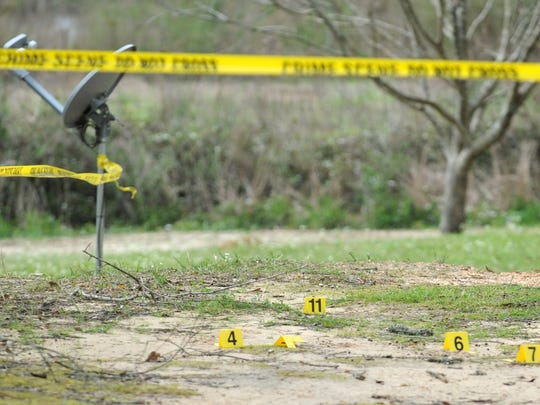 Evidence markers are scattered in the front yard of a home on T.W. Bass Road in rural Jefferson Davis County where Arvin Smith, 80, Maxine Smith, 74, and Roland Smith, 48, were shot to death in March 2012.