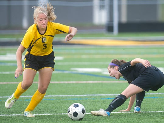 Central York's Brooke Heilman, right, goes down after she and Red Lion's Kayla Purcell battled for the ball during a girls' soccer game on Saturday. (DAILY RECORD/SUNDAY NEWS -- JASON PLOTKIN)