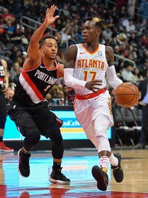 Atlanta Hawks guard Dennis Schroder drives the lane against Portland Trail Blazers guard CJ McCollum during the first half at Philips Arena.