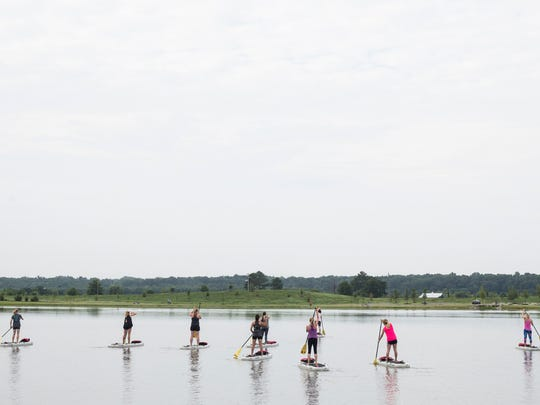 July 15, 2017 - Stand up paddle boarders head out onto Hyde Lake before the start of a stand up paddle board yoga class at Shelby Farms park.
