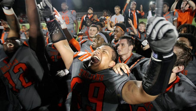 Lely High School's Eric Cruz, center, and teammates celebrate beating Immokalee to win the District 5A-15 championship game at Lely High School in Naples on Friday.