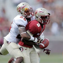 TALLAHASSEE, FL - APRIL 12:  P.J. Williams #26 of the Gold team strips a ball from Jesus Wilson #3 of the Garnet team during Florida State's Garnet and Gold spring game at Doak Campbell Stadium on April 12, 2014 in Tallahassee, Florida.  (Photo by Stacy Revere/Getty Images)