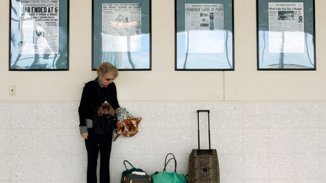 Kitty Warman, standing near historical Fort Myers News-Press front pages while toting poodle, Coco in a belly pouch, arrives at Southwest Florida International Airport Friday in Fort Myers.