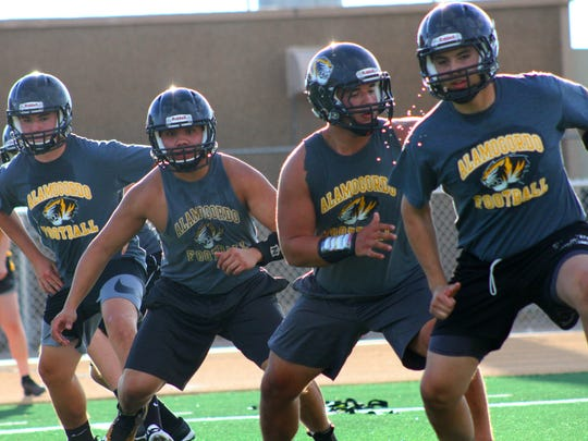 Lineman work on a blocking drill during the first day of official football practices Monday at Tiger Stadium.